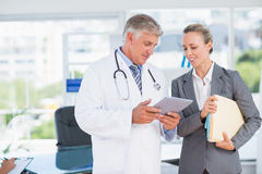 Confident doctor and pretty businesswoman discussing Royalty Free Stock Image