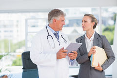 Confident doctor and pretty businesswoman discussing royalty free stock photos
