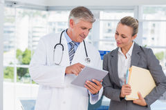 Confident doctor and pretty businesswoman discussing Royalty Free Stock Images