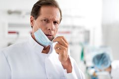 Confident doctor pulling off sterile protective mask royalty free stock photography