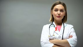 Confident doctor with red ribbon looking into camera, hiv aids awareness royalty free stock photography