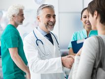Confident doctor shaking patient`s hand. Smiling confident doctor shaking patients hand at the hospital and medical team royalty free stock photos