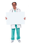 Confident doctor showing blank whiteboard Royalty Free Stock Photography
