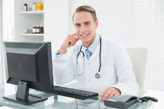 Confident doctor sitting with computer at medical office Stock Images