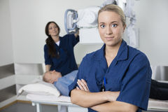 Confident Doctor Smiling While Colleague Taking Patient's Xray Stock Images