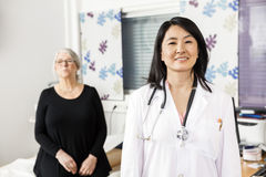 Confident Doctor Smiling While Patient Sitting In Background. Portrait of confident female doctor smiling while patient sitting in background at clinic stock photos