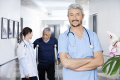 Confident Doctor Standing With Colleague And Senior Patient In B. Portrait of confident doctor standing arms crossed with colleague and senior patient in Royalty Free Stock Photography