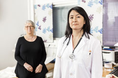 Confident Doctor Standing While Patient Sitting In Background. Portrait of confident female doctor standing while patient sitting in background at clinic stock images