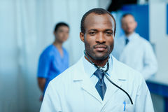 Confident doctor with stethoscope with colleagues behind in clinic Stock Photos