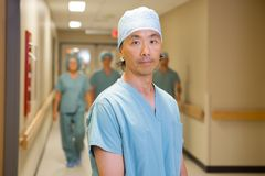 Confident Doctor With Team Walking In Corridor Stock Photography