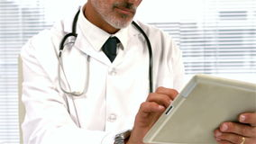 Confident doctor using tablet. In office stock video