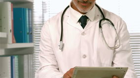 Confident doctor using tablet. In office stock video footage