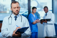 Confident doctor writing in folder in clinic with colleagues behind Stock Photos