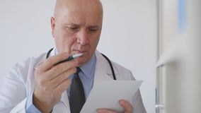 Confident Doctor Writing a Prescription for a Medical Treatment royalty free stock photography