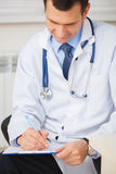 Confident doctor writing a prescription. Royalty Free Stock Photography