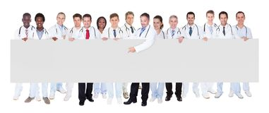 Confident doctors against white background Royalty Free Stock Photo