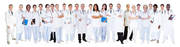 Confident doctors against white background. Panoramic shot of confident doctors standing against white background Royalty Free Stock Image