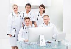 Confident Doctors At Desk Stock Photo
