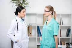 Confident doctors discussing work together in clinic. Side view of confident doctors discussing work together in clinic Royalty Free Stock Image