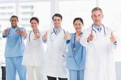 Confident doctors gesturing thumbs up at hospital Stock Photos