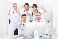 Confident Doctors Gesturing Thumbs Up Royalty Free Stock Photos