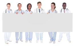 Confident doctors holding blank billboard. Full length portrait of confident doctors holding blank billboard over white background Stock Image