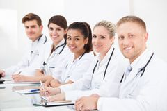 Confident Doctors Sitting In A Row Royalty Free Stock Image