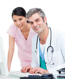 Confident doctors working at a computer Royalty Free Stock Image