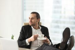 Confident dreamy businessman relaxing with cup of coffee at work. Confident dreamy businessman relaxing with legs up on desk, holding cup of coffee at work in Royalty Free Stock Photography