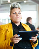 Confident and edgy female designer working on a digital tablet in red creative office space Royalty Free Stock Photo