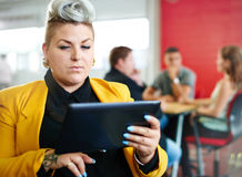 Confident and edgy female designer working on a digital tablet in red creative office space Stock Photo