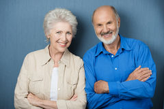 Confident elderly couple with folded arms. Standing side by side smiling at the camera against a green background Royalty Free Stock Images
