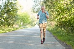 Confident elderly male runner joggs on road, has workout in morning, being very active, enjoys beautiful nature, being on pension. Pensioner has outdoor Royalty Free Stock Photo