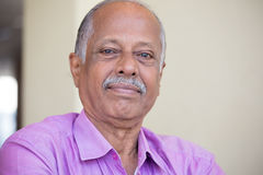Confident elderly man. Closeup headshot portrait of elderly gentleman sitting down in pink shirt smiling, content,  indoors white wall background Stock Photography