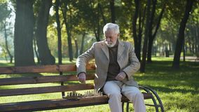 Confident elderly man playing chess and relaxing in park, happy life in old age