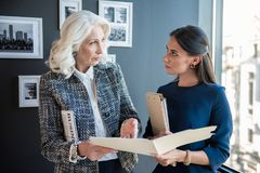 Confident elegant aged lady is standing with younger woman Royalty Free Stock Image