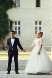 Confident elegant groom and beautiful shy bride holding hands ou Royalty Free Stock Images
