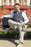 Confident elegant man sitting on the bench with a book Royalty Free Stock Photos