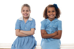 Confident elementary school girls. Smiling school girls sitting in bench, arms folded Royalty Free Stock Photos