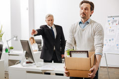 Confident employer firing the employee from the company Stock Image