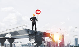 Confident engineer holding street safety sign. Rear view of engineer in helmet holding stop sign while standing among flying paper planes on broken bridge with Royalty Free Stock Image