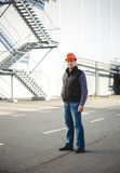 Confident engineer posing against warehouse Stock Image