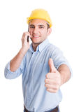 Confident engineer showing thumb up while talking on phone Royalty Free Stock Photos