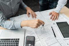 Confident engineer team working with Blue Print with architect equipment discussing and Planning work flow construction project. w. Ith partner at the table in royalty free stock photo