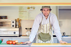 Confident entrepeneur in his takeaway food stall. Young male entrepeneur standing confidently in his food stall where he makes and sells takeaway food Royalty Free Stock Photo