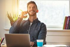 Confident entrepreneur chatting on a mobile. Phone while working at his desk looking up into the air with an elated smile of satisfaction Stock Photos