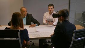 Confident entrepreneur in virtual reality glasses. Group of young developers working on building and road drawings in. Modern glass office. Diverse business stock video footage