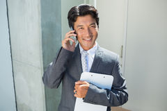 Confident estate agent standing at front door on the phone Royalty Free Stock Photo