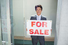 Confident estate agent standing at front door showing for sale sign Stock Images