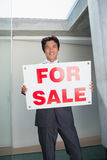 Confident estate agent standing at front door showing for sale sign Stock Photo